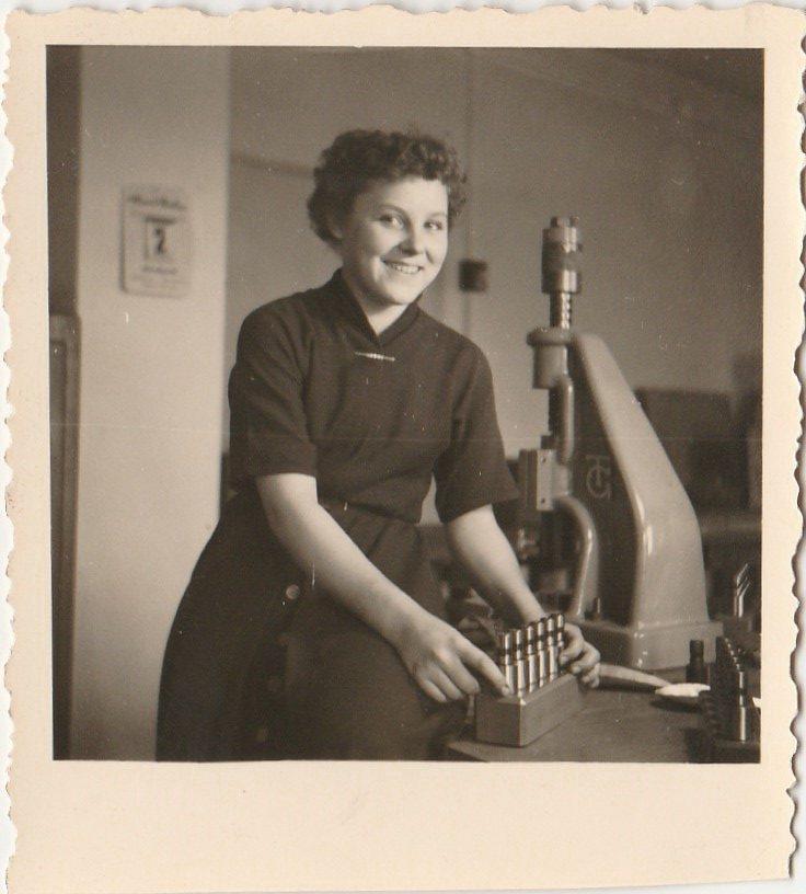 Eine junge Frau arbeitet an einer Maschine. Sicherheit am Arbeitsplatz.